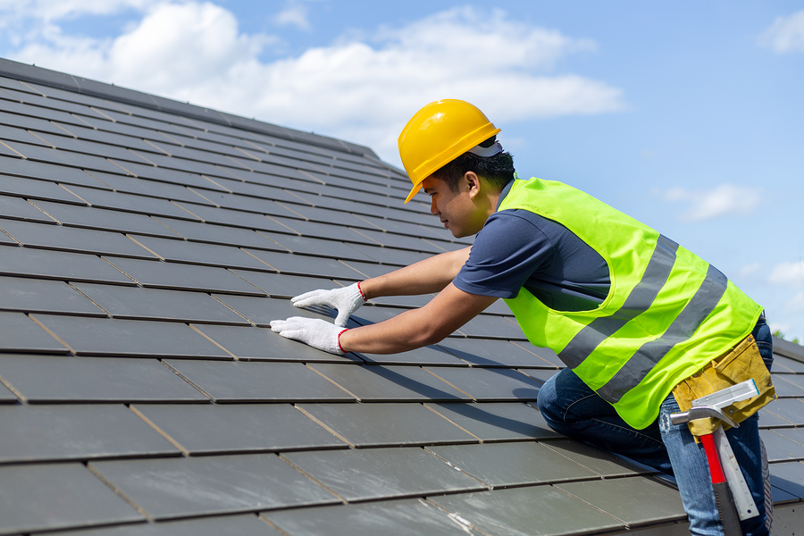 man placing the roof tiles
