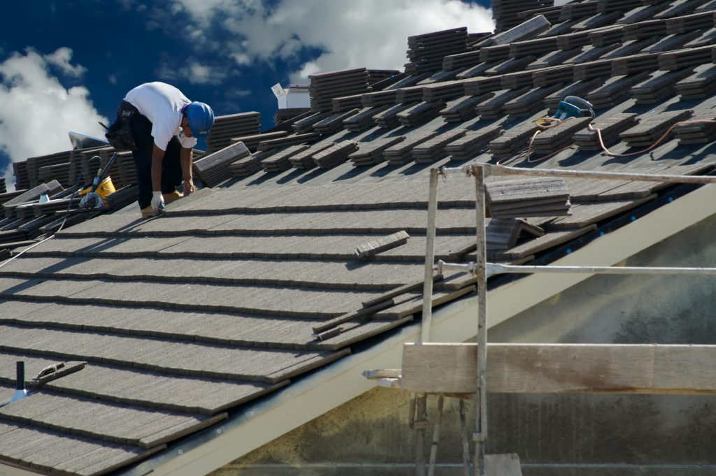 man putting the roof tiles